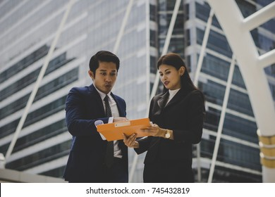 Business colleague talking and viewing documents outdoor