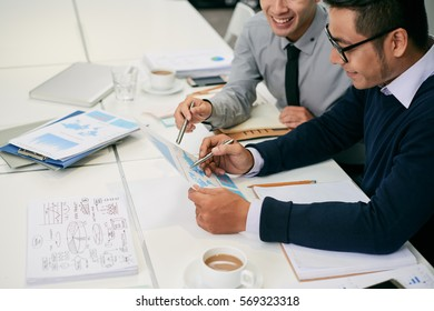 Business colleagues analyzing chart at meeting