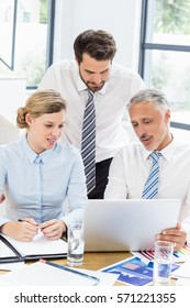 Business colleagues discussing office work on laptop in office