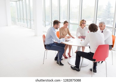 Business colleagues discussing while sitting at table by window in new office