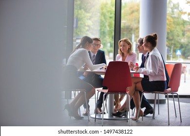 Business colleagues discussing while sitting at table in office lobby during meeting