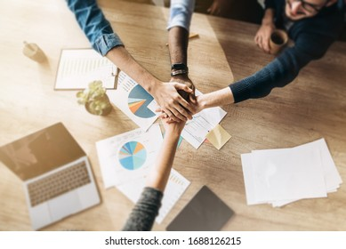 Business colleagues gathered at the same table during the work process, and rejoice in the success of their company. Top view