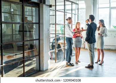 business colleagues having conversation in hall during coffee break