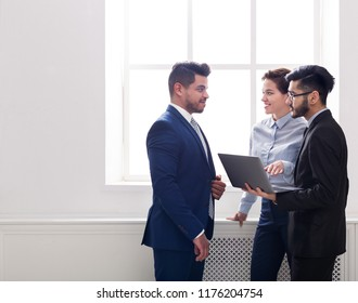 Business colleagues having conversation and using laptop in office near window