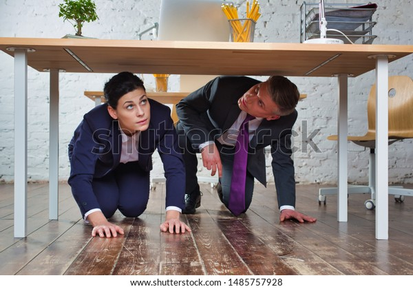 Business colleagues hiding under the table in office