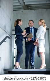 Business colleagues interacting with each other in office lobby