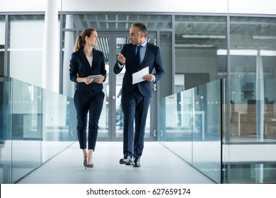 Business colleagues interacting with each other while walking in the corridor at office