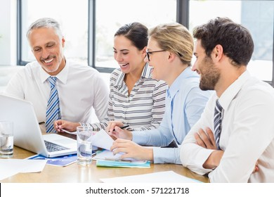 Business colleagues laughing while discussing office work on laptop in office