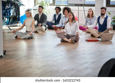 business colleagues meditating at work, sitting on the floor; copy space. modern, business, meditation concept