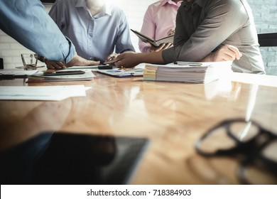 Business colleagues meeting to determine their duties to summarize annual performance in the company's meeting room. The documents, business contracts placed on a wooden table.