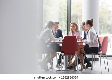 Business colleagues planning while sitting at table during meeting in office