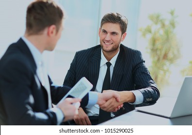 Business colleagues sitting at a table during a meeting with two male executives shaking hands.