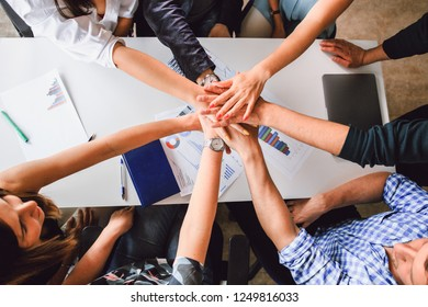 Business colleagues sitting at the table holding hands of each other, top view