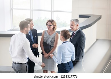 Business colleagues talking while standing at reception lobby in office