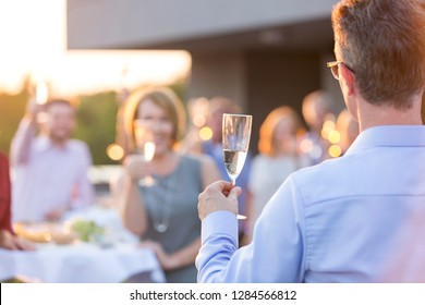 Business colleagues toasting wineglasses during rooftop success party
