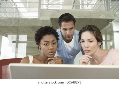 Business colleagues using laptop in office