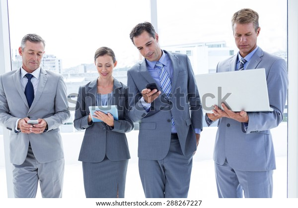 Business colleagues using their multimedia devices in the office