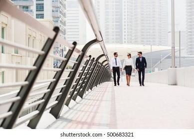 Business colleagues walking and talking at Dubai Marina.
