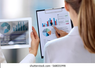 Business colleagues working and analyzing financial figures on a graphs