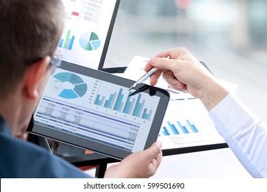 Zakelijke collega's werken en analyseren van financiële cijfers op een digitale tablet
