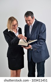 Business colleagues working together and reading a book in a meeting