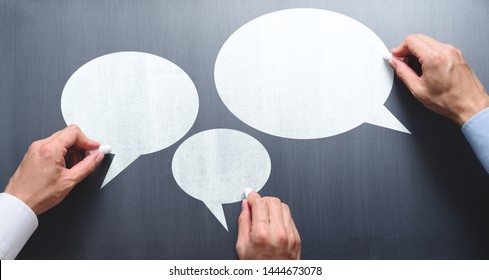 Business communication concept image. Businessmen drawing speech balloons on chalkboard.