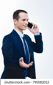 Business communication. Delighted positive smart businessman holding a phone and having a conversation while discussing business problems