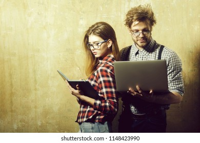 business and communication, stylish fashionable nerd couple of students in geek glasses. Pretty girl or woman with notebook and handsome man with computer in checkered shirts on beige background