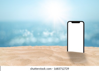 Business Communication and Summer Travel Trip Concept : Black smartphone with blank white screen on sand beach with blurry seascape view and bokeh sunlight in background.