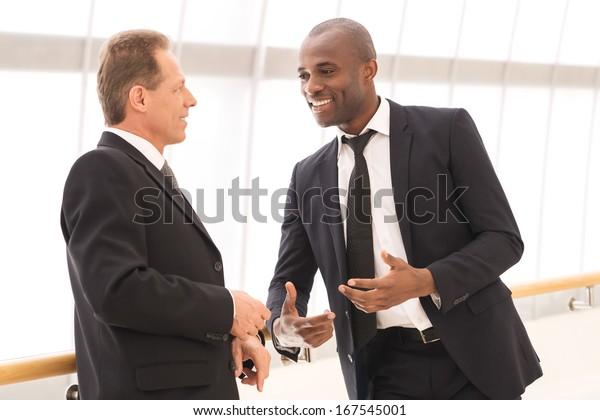 Деловое общение. Два веселых бизнесменов разговаривают друг с другом и жест