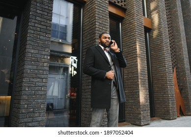 Business communications. Happy young African man in formal wear talking on the mobile phone and smiling while standing outdoors