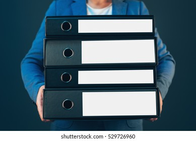 Business company accountant holding document binders with archived paperwork and other corporate legal sheets
