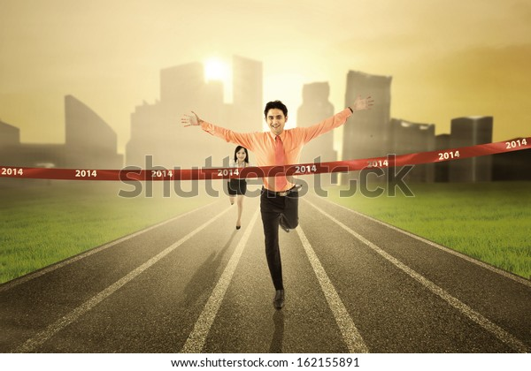 Business competition concept: Businessman crossing the finish line on the track