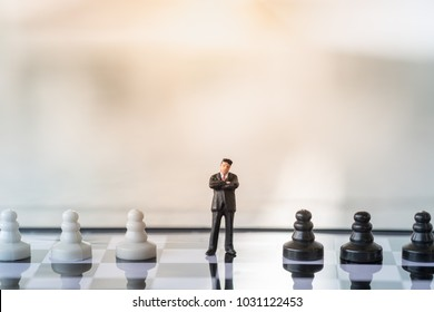 Business and Competition Concept. Businessman miniature figure standing on chessboard with black and white chess pieces