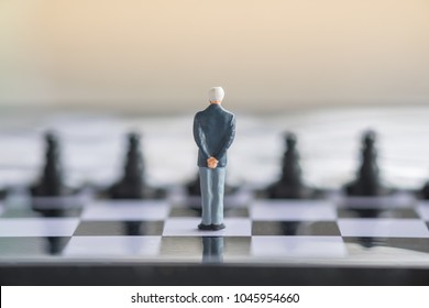 Business and Competition Concept. Businessman miniature figure standing on chessboard with black chess pieces