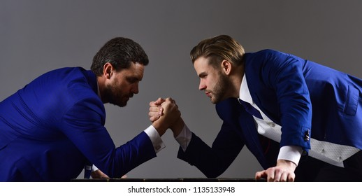 Business competition concept. Businessmen fighting for leadership. Men in suit or businessmen with tense faces compete in armwrestling on dark background.