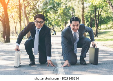 Business competition concept of two businessman knee down on the road in park and ready to compete. Two businessman in formal suit holding briefcase and ready to run. Business competitor concept.