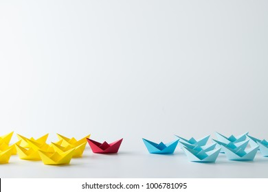 Business competition concept using two different color origami paper boats