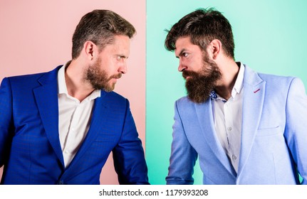 Business competition and confrontation. Businessmen stylish appearance jacket pink blue background. Tense face expression competitors. Business partners competitors in suits with tense bearded faces.