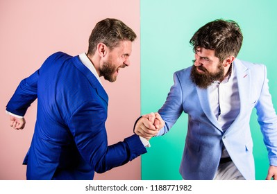 Business competition and confrontation. Hostile or argumentative situation between opposing colleagues. Business partners competitors office colleagues tense faces ready to compete in arm wrestling.