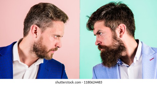 Business competition and confrontation. Business partners competitors or office colleagues in suits with tense bearded faces close up. Hostile or argumentative situation between opposing colleagues.