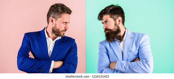 Business competition and confrontation. Business partners competitors in suits with tense bearded faces. Businessmen stylish appearance jacket pink blue background. Tense face expression competitors.