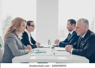 Business competition, four stylish attractive business persons in suits having disagreement and conflict, sitting together at desktop in front of each other, face to face with disrespect expression