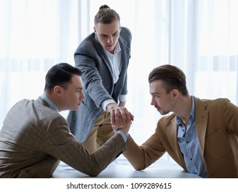 business competition. young man refereeing two rivals in their  arm wrestling fight. cruel corporate world