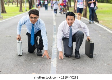 Business competition:Front view of two worker wearing formal suit and kneeling on the start line to compete