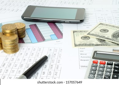Business composition of graphs, tables, money and pen close-up