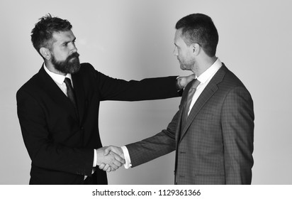 Business and compromise concept. Executives shake hands in agreement on light grey background. Businessmen wear smart suits and ties. Men with beard and satisfied faces make successful deal.