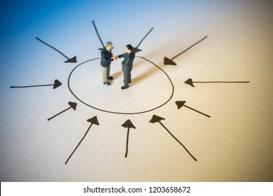 Business concept of achievement. Businessman handshaking at center of arrows.