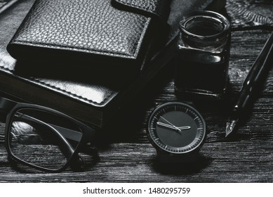 Business concept background. Black leather book, inkwell with a quill pen, wallet, eye glasses and a hand watch on a black wooden table.