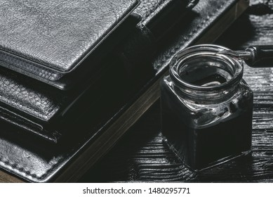 Business concept background. Black leather book, inkwell with a quill pen and wallet on a black wooden table.